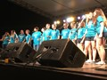 The Colonial Kids, wearing light blue shirts, sing on the Main Stage at the festival.