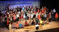 Elementary students on stage singing during the holiday concert.