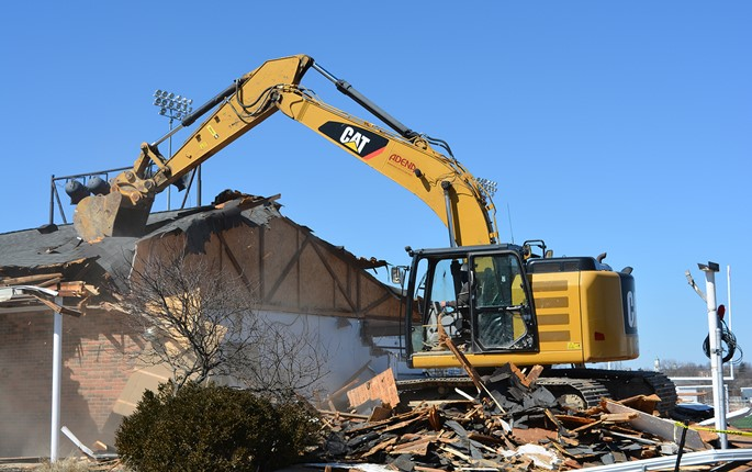 Large track hoe demolishes the old stadium entrance to Energy Field.