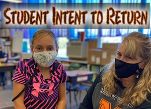 Student and Teacher with masks on in a classroom.