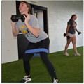 Student performing leg exercises with power bands and dumbells.