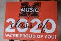 """An orange sign with the MV Music """"M"""" logo and the text class of 2020, we're proud of you!"""