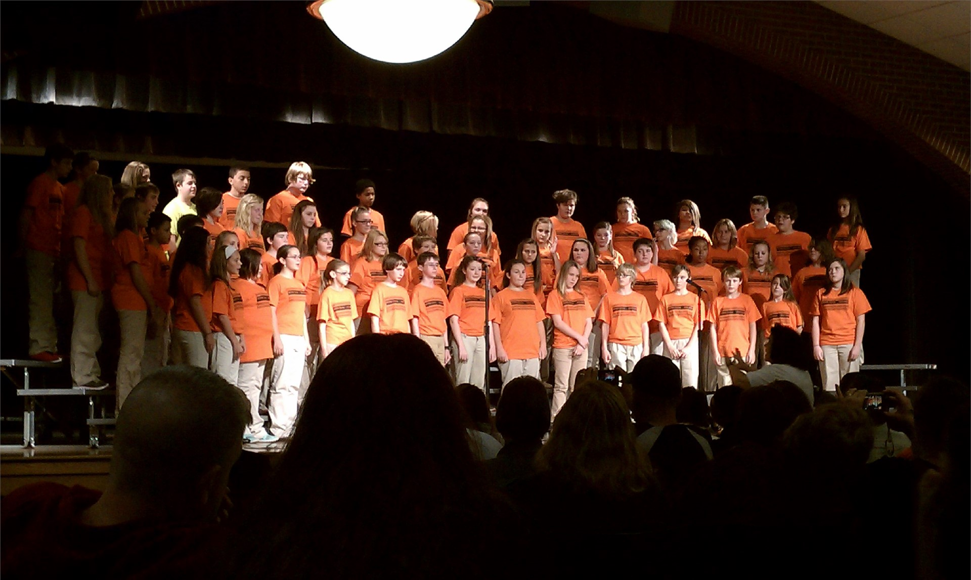 7th Grade Choir performs onstage.