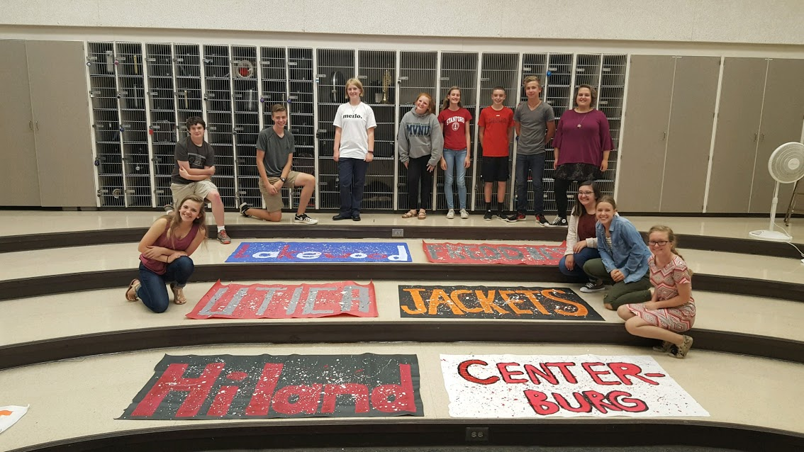 Students surrounding painted signs for Hiland, Centerburg, Utica, Jackets, Lakewood, and Freddies.