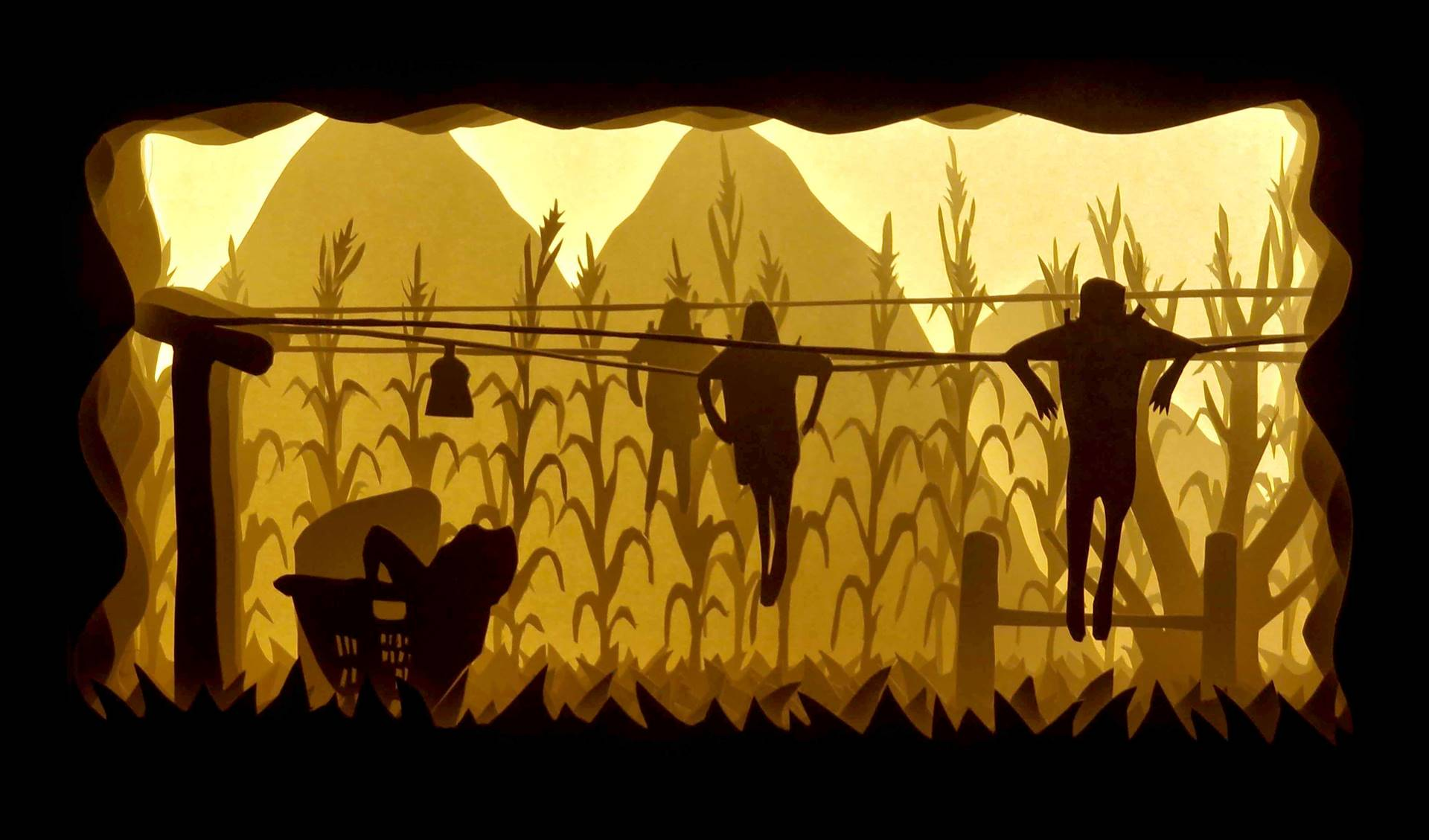Layers of cut paper mountains, corn stalks in a field, and people attached to a laundry line