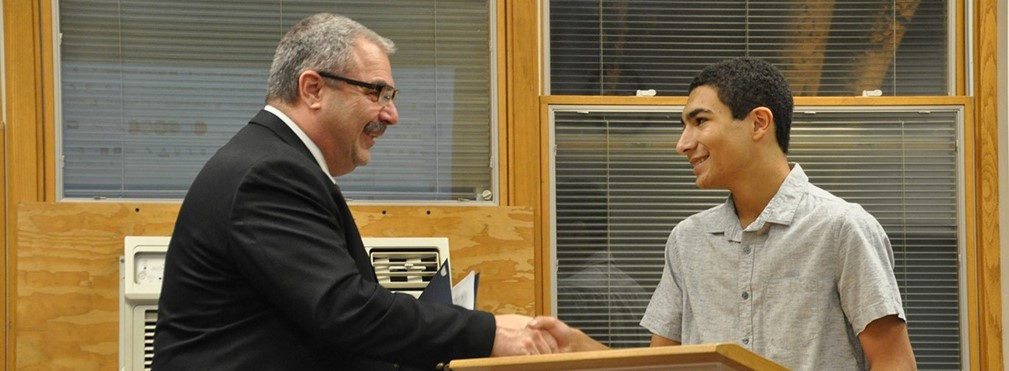 Superintendent Bill Seder congratulates Owen Decatur on earning the National Merit Scholarship Commended Student.
