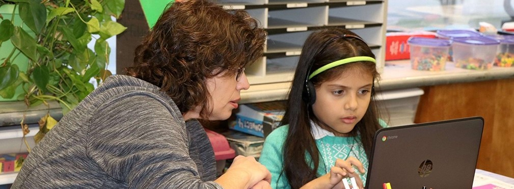 Teacher assisting student on digital lesson.