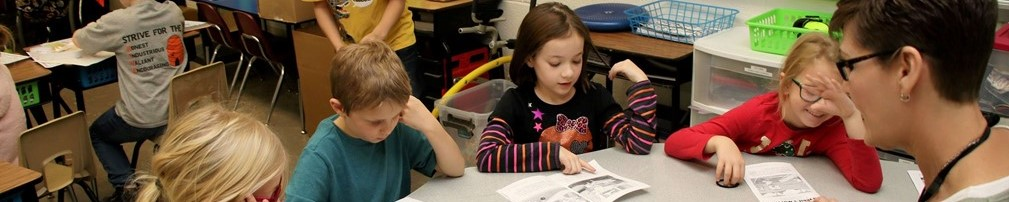 Pleasont Street students reading with their teacher.