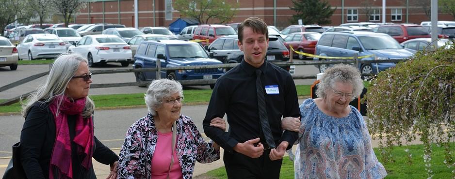 Matt escorting senior citizens to the spring luncheon
