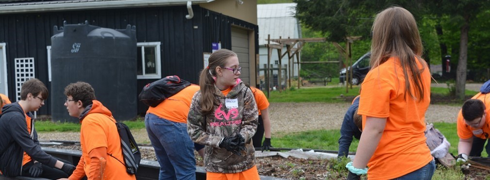 Middle School students weeding raised beds at the Kenyon Farm.