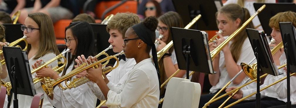 Middle School students playing trumpets and trombones during the Spring Concert.