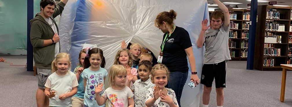 Preschool students emerging from a bubble biome.