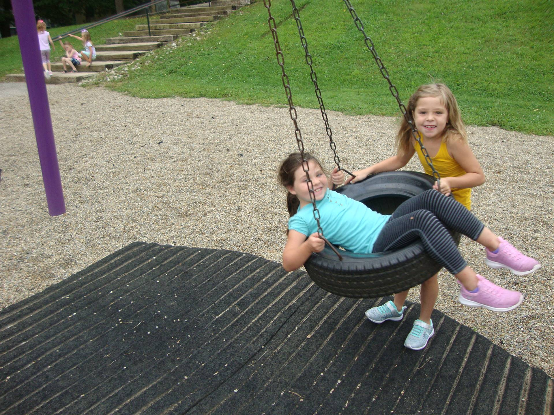2 girls on tire swing