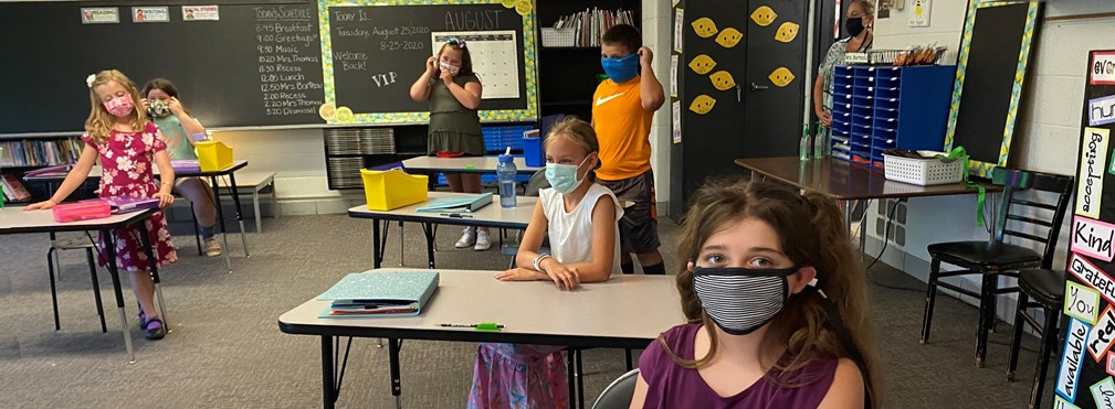 Students wearing face coverings and practicing social distancing in a classroom.