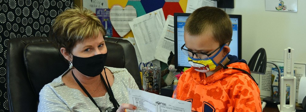 Student reviewing work with Mrs. Fowler.