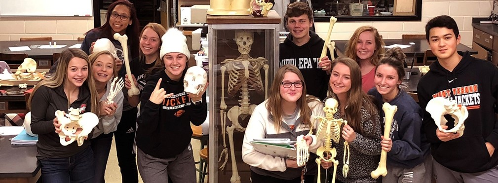 Physiology students holding bones during a study session.