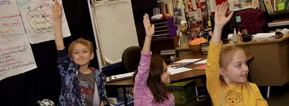 Elementary students with hands raised.