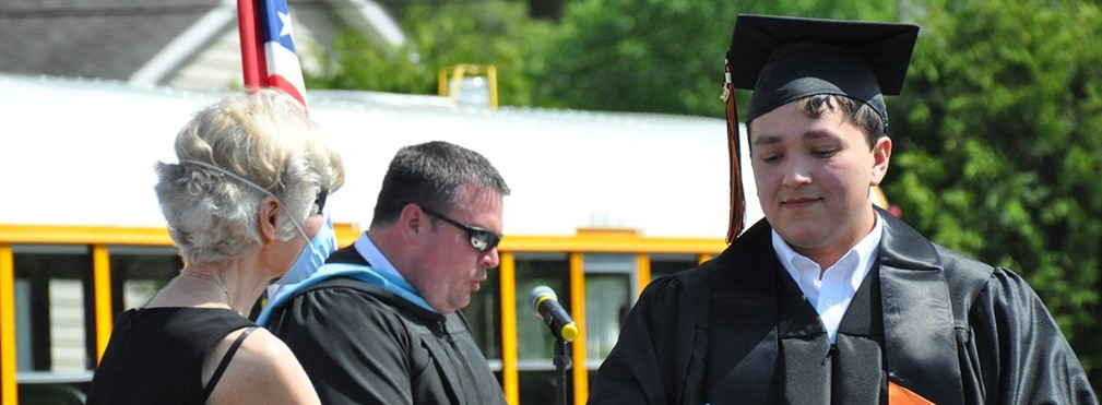 Board President, Margie Bennett presenting a diploma.