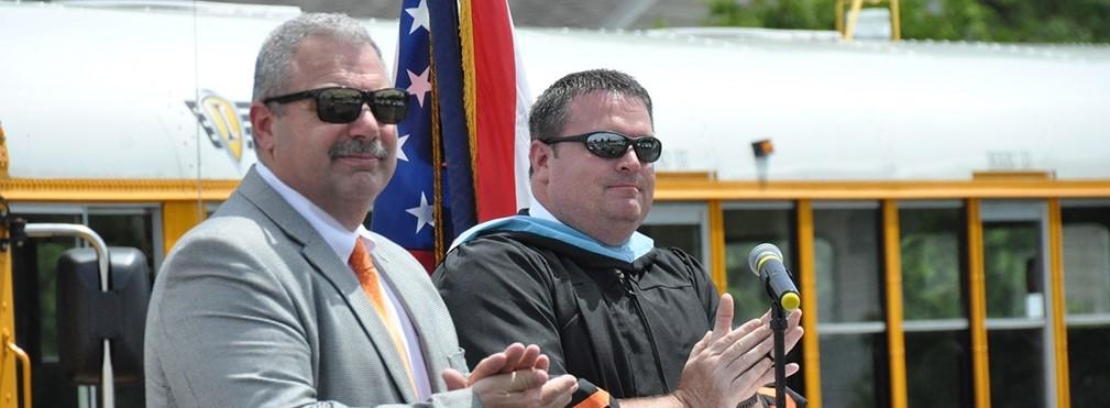 Superintendent Bill Seder and Principal Scott Will applaud the graduates.