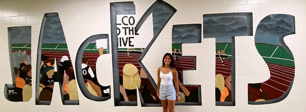 Mia Tracey stands in front of the Jackets Hallway Mural.