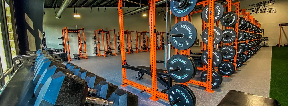 Racks of weight stations in the fieldhouse weight room.