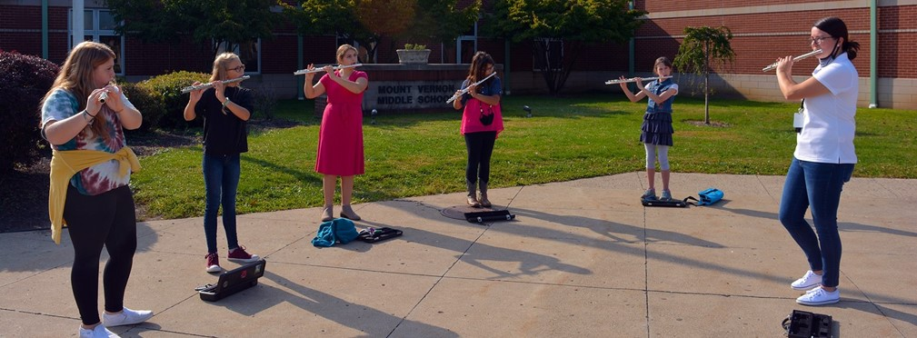Middle School flute section of band class being instructed outside.
