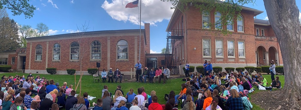 East Elementary students sitting on the front lawn during Arbor Day celebration.