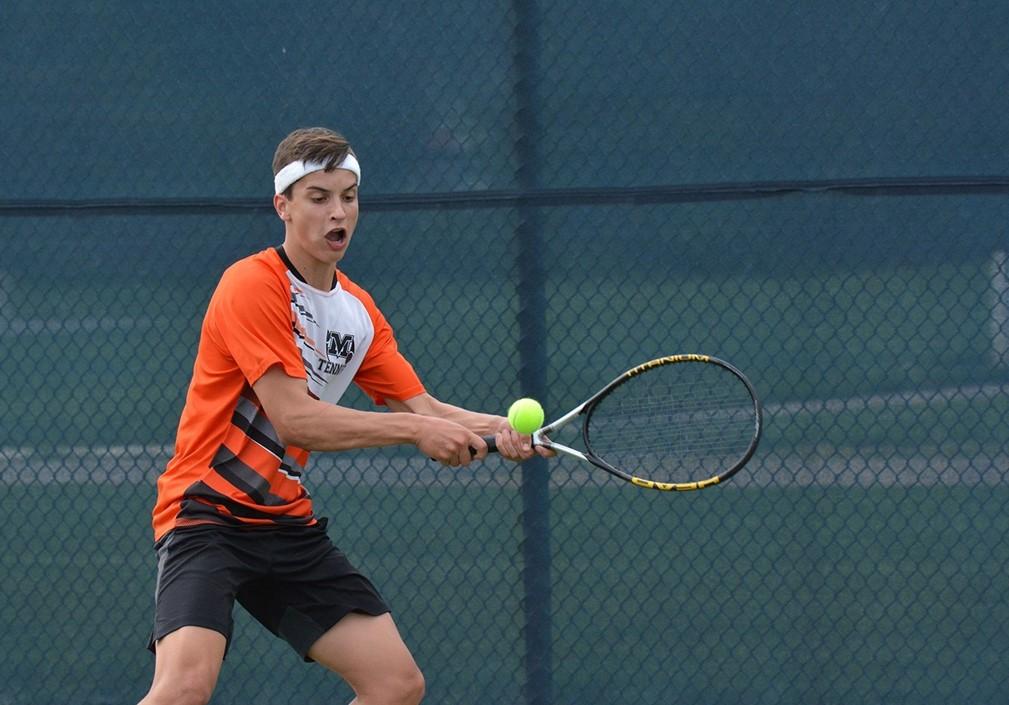 Boys Tennis player hitting the ball.