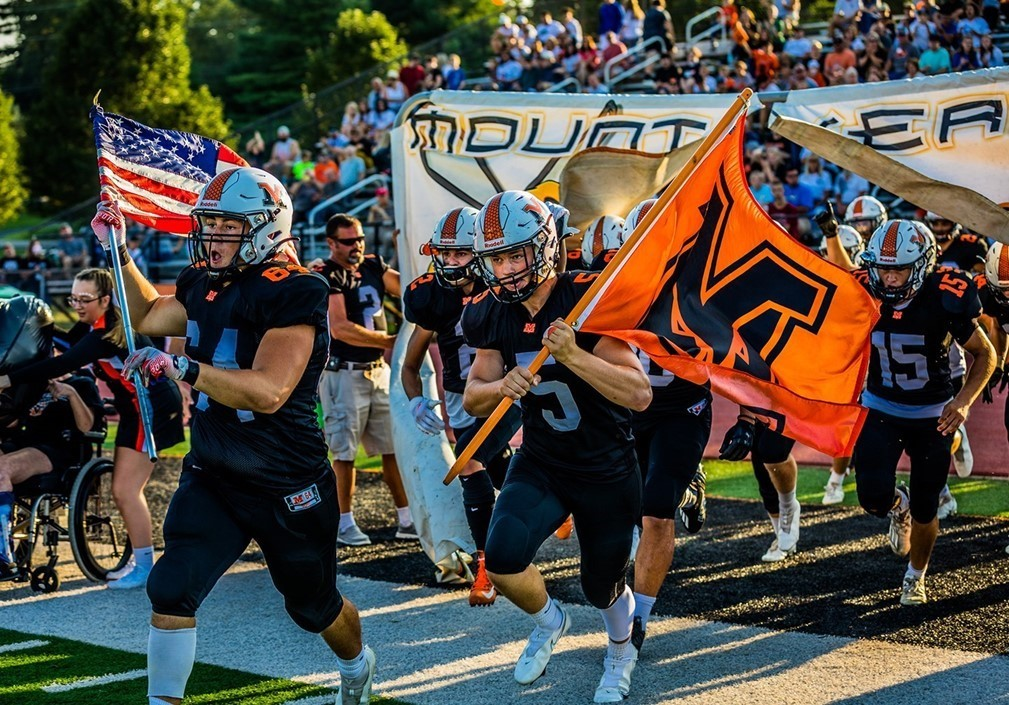 Yellow Jacket Football Team running through the banner to take the field.