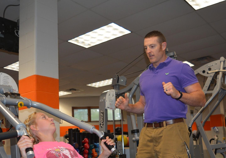 Mr. Reynolds instructing a student on the shoulder press machine.