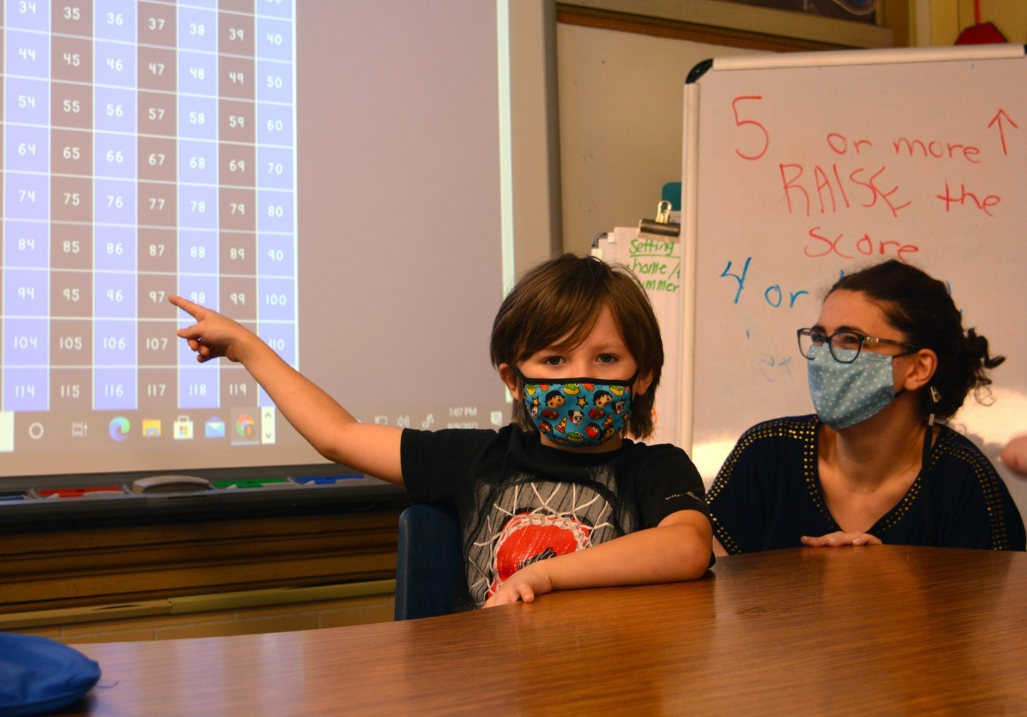 Student pointing to a number board with his teacher.