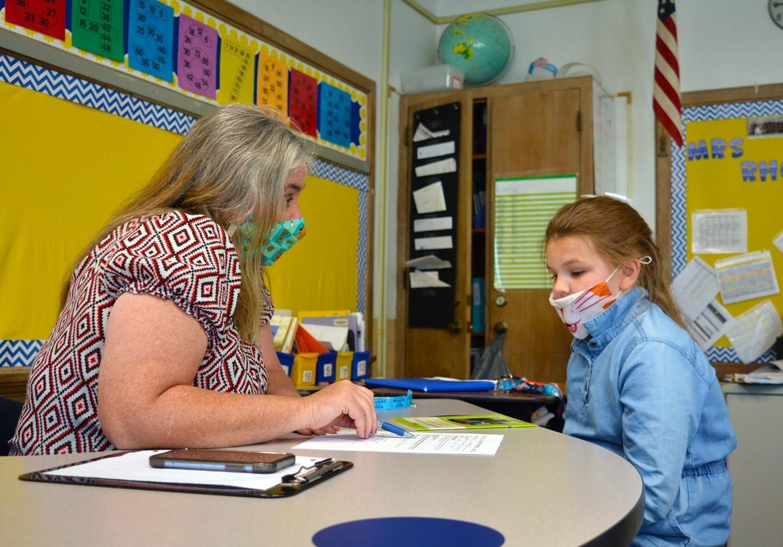 Teacher helping a student with an assignment.