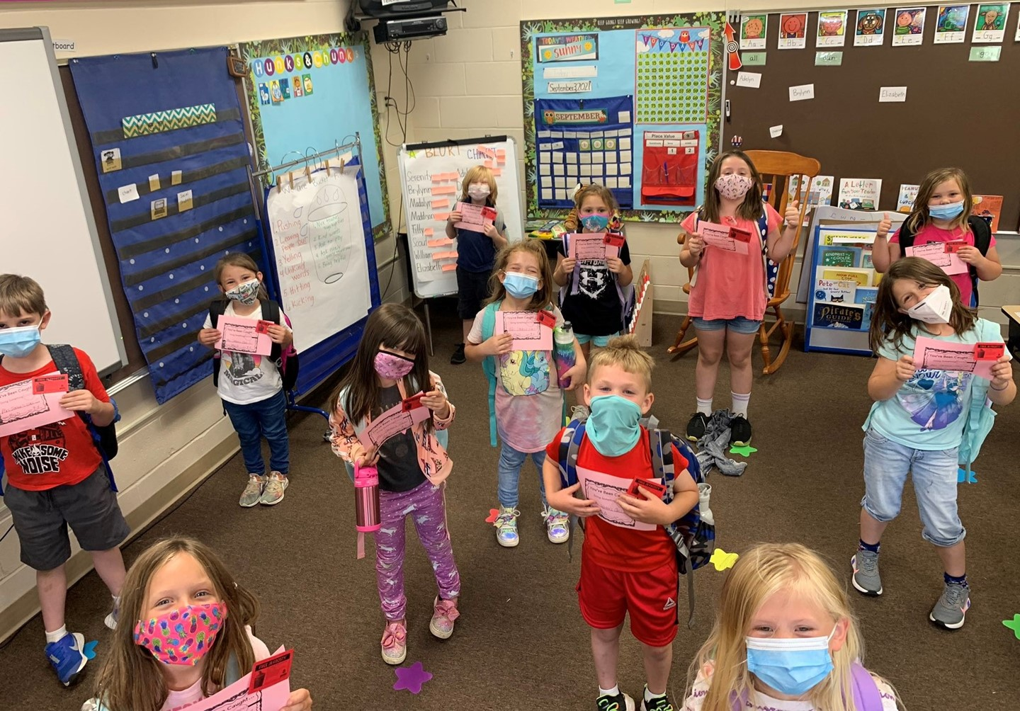 Students in masks showing their success certificates.