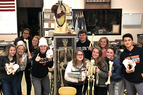 Students in physiology class holding various skeletal parts.