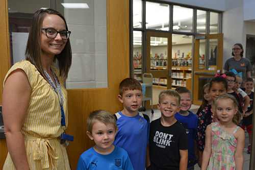 Teacher and students in the entrance to Twin Oak's office.