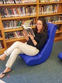 Mrs Rochte reading a book in her new gaming chair